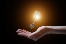 business woman holding shining key in a dark